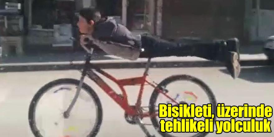 Bisikleti, üzerinde uzanarak sürdü